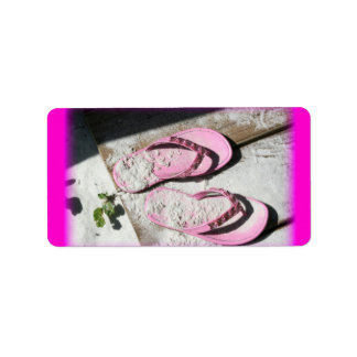 Sandalias arenosas rosadas del flip-flop en la pla etiquetas de dirección