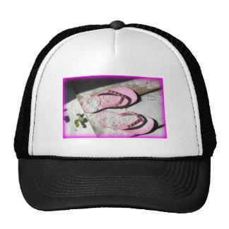 Sandalias arenosas rosadas del flip-flop en la pla gorro