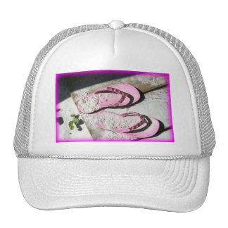 Sandalias arenosas rosadas del flip-flop en la pla gorra