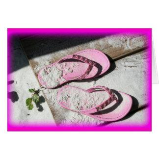 Sandalias arenosas rosadas del flip-flop en la pla tarjeta