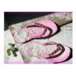 Sandalias arenosas rosadas del flip-flop en la pla tarjeta postal