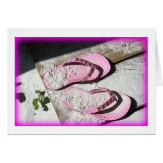 Sandalias arenosas rosadas del flip-flop en la tarjeta pequeña