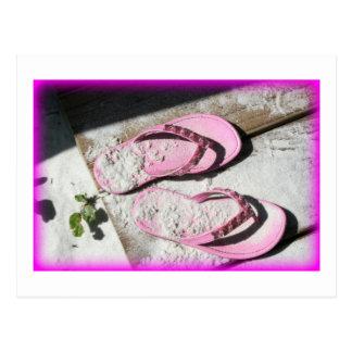 Sandalias arenosas rosadas del flip-flop en la tarjeta postal