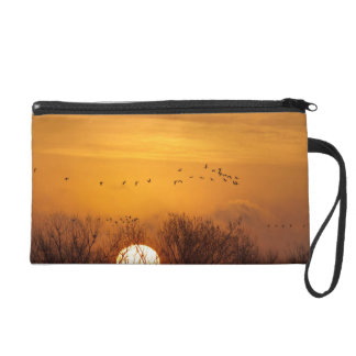 Sandhill cranes silhouetted aginst rising sun wristlet purse