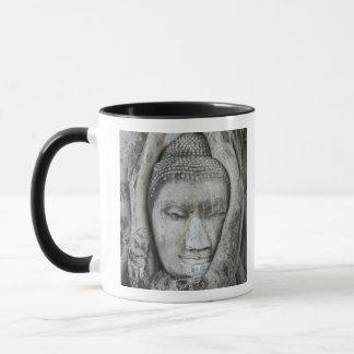 Sandstone head of Buddha surrounded by tree Mug