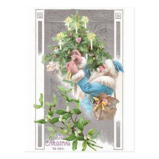 Santa antiguo en capa azul con el árbol de Navidad