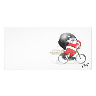 Santa bicycling with his sack in the snow. card