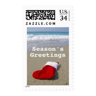 Santa Claus sock laying on beautiful beach Postage