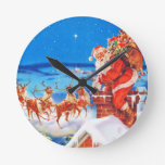 Santa Claus Up On The Rooftop In The Snow Round Wall Clocks