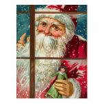 Santa con la muñeca que mira en la ventana tarjeta postal