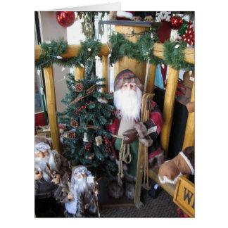 Santa con la tarjeta de Navidad de los esquís