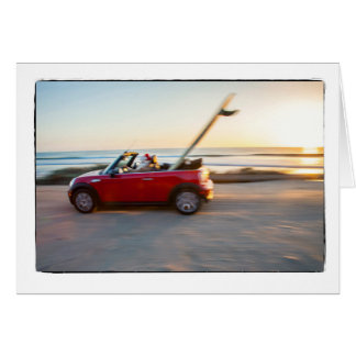 Santa driving Mini at the beach with a SUP Greeting Card