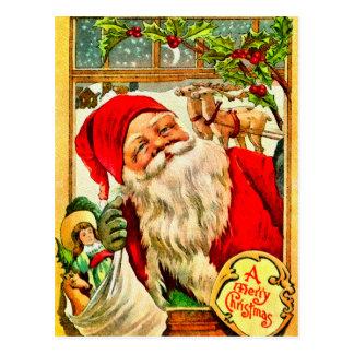Santa en la ventana con el bolso de juguetes postal