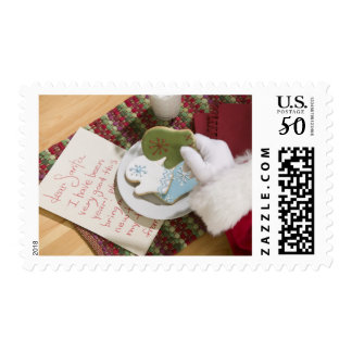 Santa hand with cookies and note postage