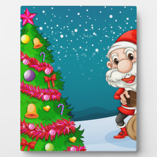 Santa near the big christmas tree plaque