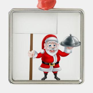 Santa que lleva a cabo la cena y la muestra adorno navideño cuadrado de metal