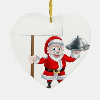 Santa que lleva a cabo la cena y la muestra adorno navideño de cerámica en forma de corazón