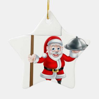 Santa que lleva a cabo la cena y la muestra adorno navideño de cerámica en forma de estrella