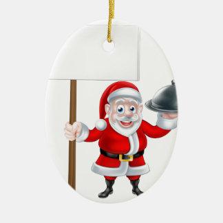 Santa que lleva a cabo la cena y la muestra adorno navideño ovalado de cerámica