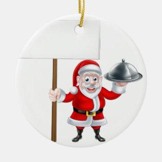 Santa que lleva a cabo la cena y la muestra adorno navideño redondo de cerámica