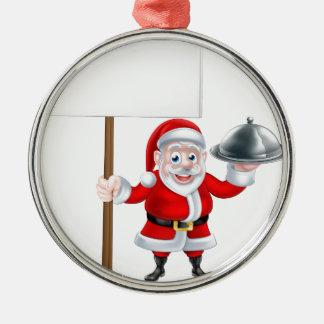 Santa que lleva a cabo la cena y la muestra adorno navideño redondo de metal