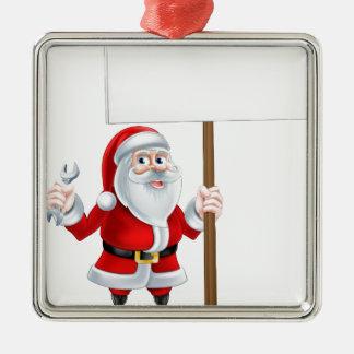 Santa que lleva a cabo la llave y la muestra adorno navideño cuadrado de metal