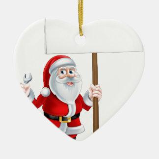 Santa que lleva a cabo la llave y la muestra adorno navideño de cerámica en forma de corazón
