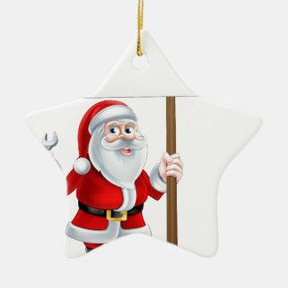 Santa que lleva a cabo la llave y la muestra adorno navideño de cerámica en forma de estrella