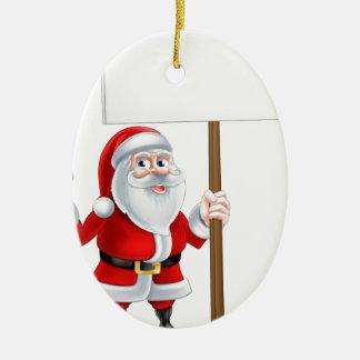 Santa que lleva a cabo la llave y la muestra adorno navideño ovalado de cerámica