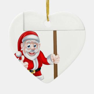 Santa que lleva a cabo la muestra adorno navideño de cerámica en forma de corazón