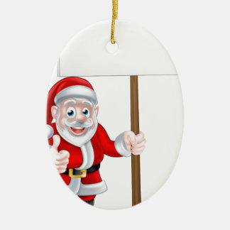 Santa que lleva a cabo la muestra adorno navideño ovalado de cerámica