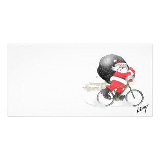 Santa que monta en bicicleta con su saco en la tarjeta fotografica