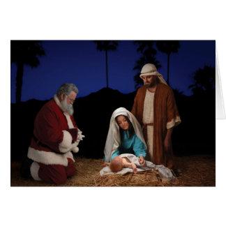 Santa que se arrodilla en la natividad felicitaciones