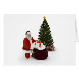 Santa setting presents by the tree card