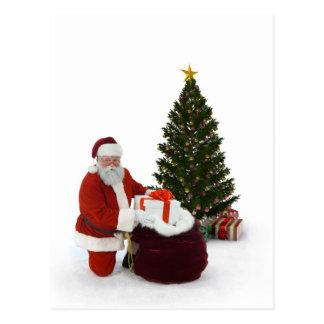 Santa setting presents by the tree postcard