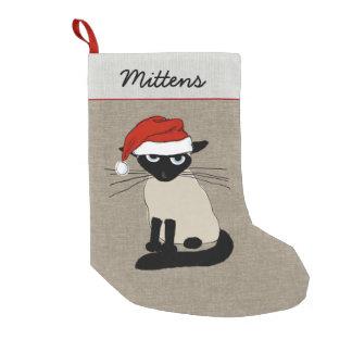Santa siamés agarra el gato del gatito con el calcetín de navidad pequeño