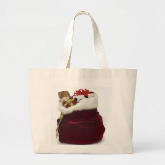 Santa unloading presents by the tree jumbo tote bag