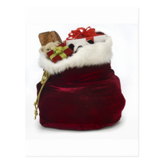 Santa unloading presents by the tree postcard