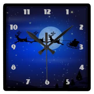 Santa y sus renos que vuelan en la noche reloj cuadrado