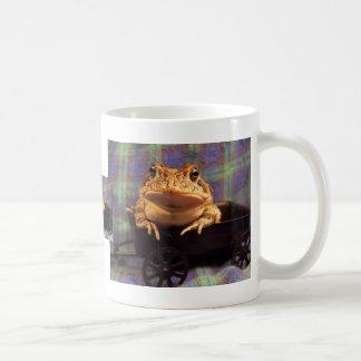 Sapo de la rana en carro negro con el fondo de la  tazas de café