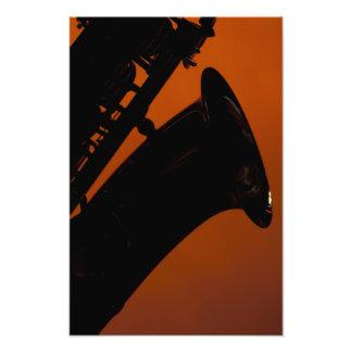 Saxofón en fondo del proyector del oro fotografias