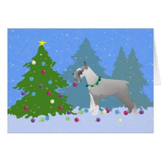 Schnauzer que adorna el árbol de navidad en el tarjeta de felicitación