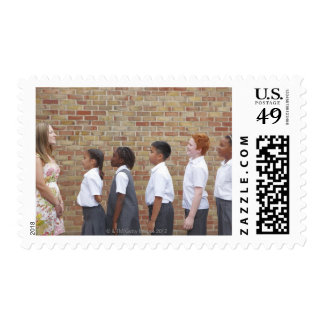 School children lining up in the playground for stamp