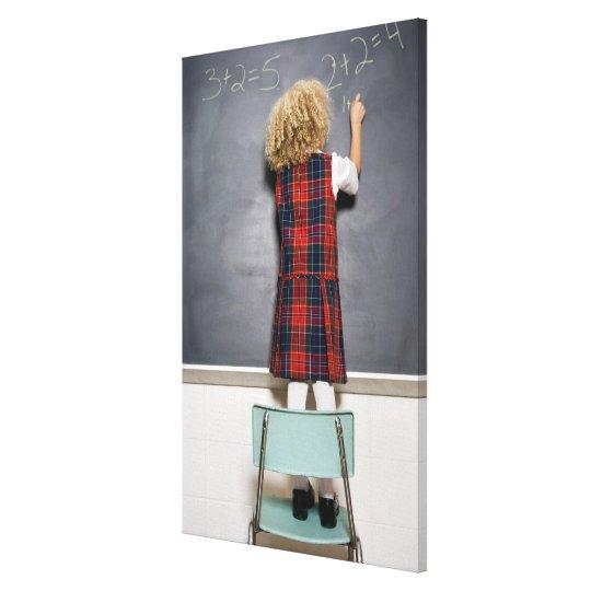 School girl (6-7) writing on blackboard, canvas print