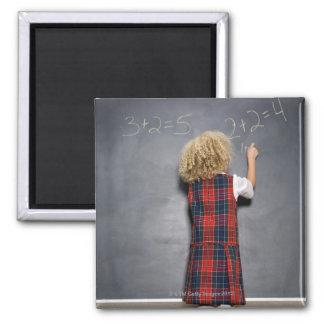 School girl (6-7) writing on blackboard, magnet