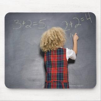 School girl (6-7) writing on blackboard, mouse pad