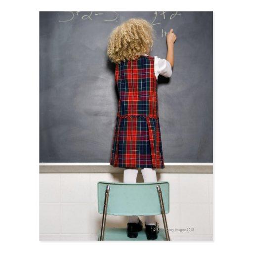 School girl (6-7) writing on blackboard, postcard