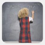 School girl (6-7) writing on blackboard, square sticker