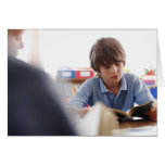 schoolboy reading in classroom greeting cards