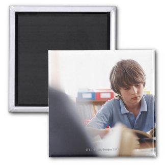 schoolboy reading in classroom magnet